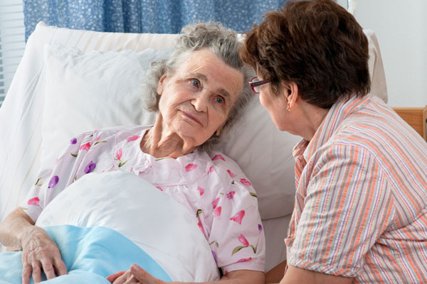 lady caring for elderly woman in bed